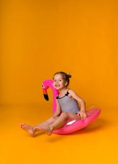 Una bambina felice in costume da bagno a righe si siede in un cerchio gonfiabile rosa e guarda la telecamera su uno sfondo giallo con spazio per il testo. orientamento verticale