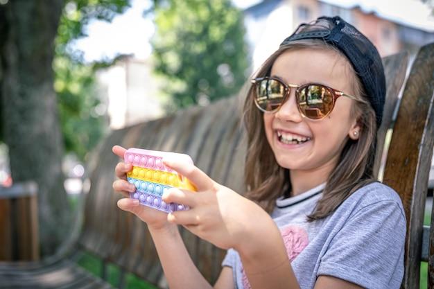 Bambina felice in occhiali da sole con uno smartphone in una custodia alla moda pop it.