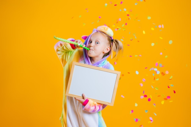 Una bambina felice in un kigurumi unicorno tiene una scheda vuota per il testo su un muro giallo