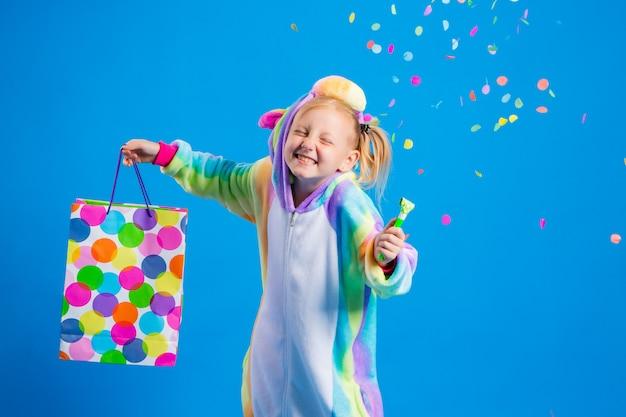 Una bambina felice in un kigurumi unicorno tiene in mano un sacchetto regalo