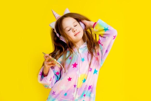 Bambina felice in un unicorno kigurumi su uno sfondo giallo