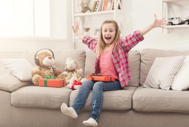 Regali di disimballaggio della bambina felice. il bel bambino scarta i regali sul divano di casa. concetto di festa. natale o festa di compleanno, copia spazio
