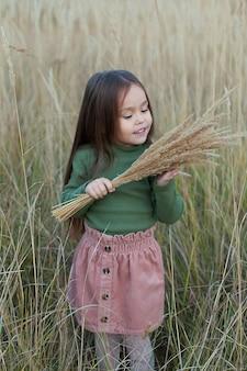 Una bambina felice che cammina sul grano dorato, godendosi la vita nel campo. il concetto di libertà. bambina carina nel campo autunnale
