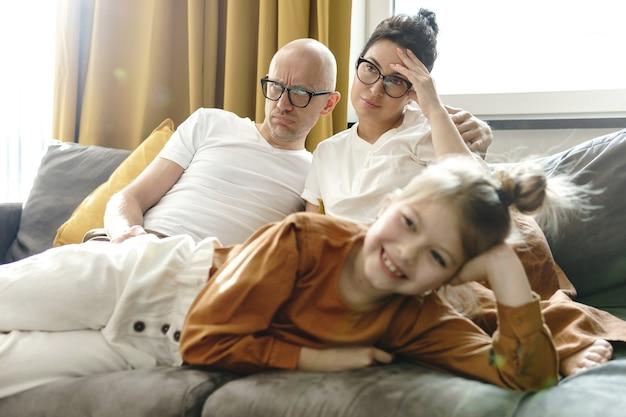 Bambina felice che guarda i cartoni animati con i suoi genitori stanchi a casa