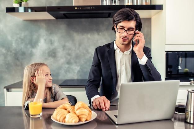 Bambina felice che guarda suo padre che lavora al telefono