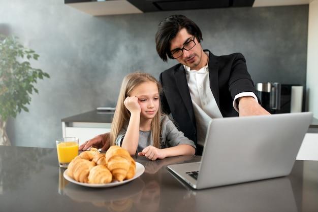 Bambina felice che guarda un film sul computer con suo padre a casa
