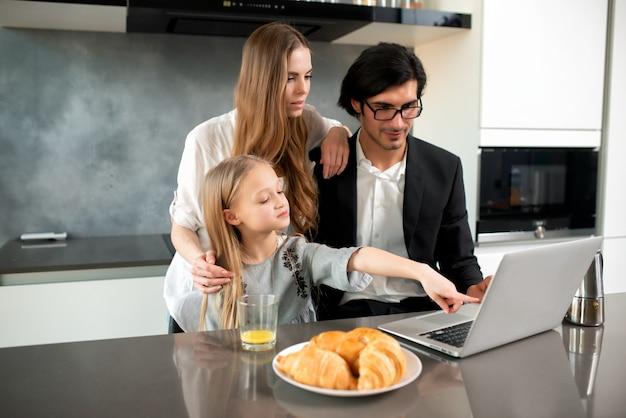 Bambina felice che guarda un film sul computer con suo padre e sua madre a casa