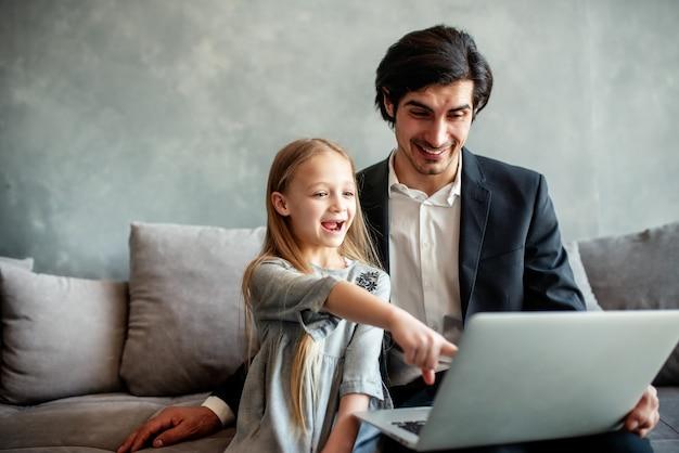 Bambina felice che guarda un film sul computer con suo padre