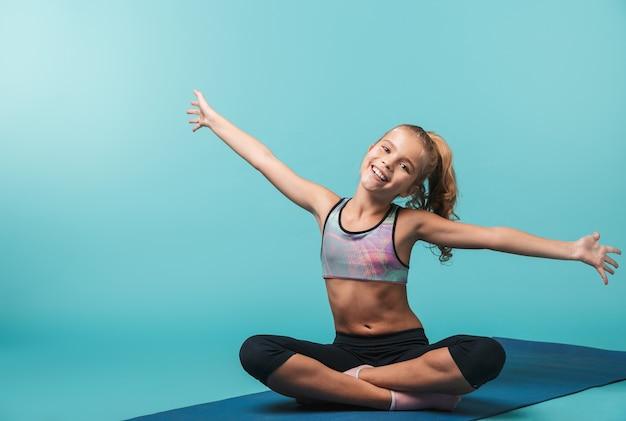 Bambina felice che indossa abbigliamento sportivo facendo esercizi su un tappetino fitness isolato sopra la parete blu