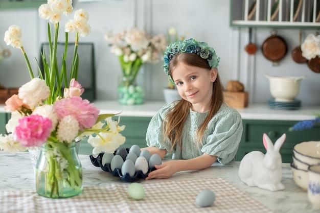 Bambina felice con bouquet di fiori in cucina bambino si sta preparando per la pasqua