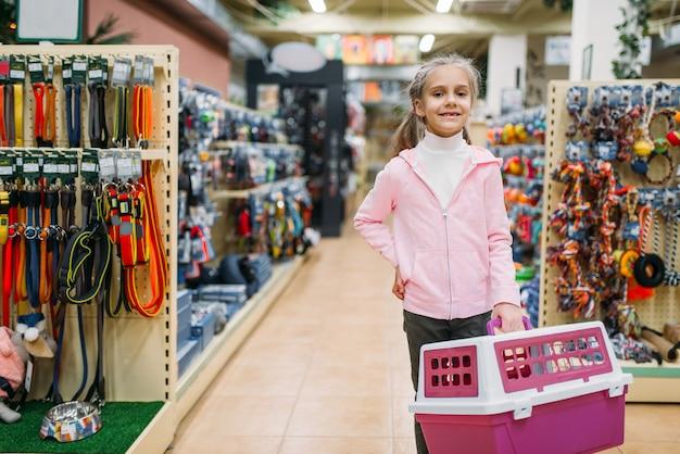 Bambina felice con trasportino per gatto nel negozio di animali