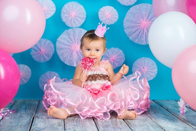 Bambina felice con una corona che mangia un grande lecca-lecca di zucchero