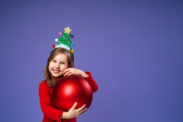 La bambina felice con la fascia decorata tiene la palla rossa di natale sulla porpora in studio.