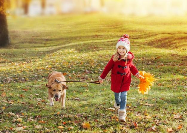 Bambina felice con il cane che corre nella sosta di autunno