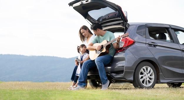 Bambina felice con la famiglia seduta in macchina
