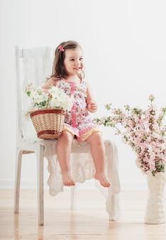 Bambina felice con i fiori dell'interno