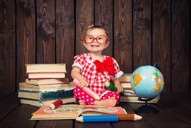 Bambina felice con libri di occhiali e matite