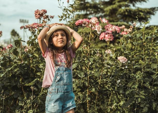 Bambina felice con un cappello e una tuta in denim in piedi tra i cespugli di rose