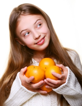 Bambina felice con le arance isolate su bianco