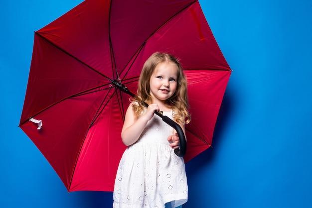 Bambina felice con l'ombrello rosso che posa sulla parete blu.