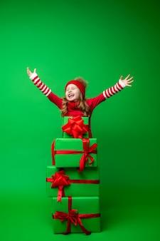 Bambina felice con una pila di scatole regalo di natale