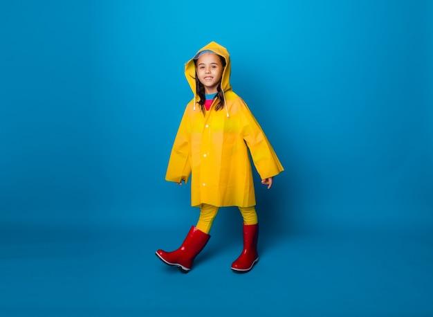 Bambina felice in un impermeabile giallo e stivali rossi su sfondo blu.