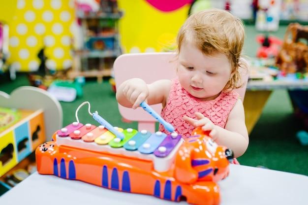 Ragazzino felice, bambina di 1-2 anni, i bambini suonano uno strumento musicale xilofono nel centro giochi, divertimento nella stanza dei bambini per il compleanno. intrattenimento al coperto.