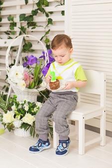 Il ragazzino felice che festeggia il suo compleanno tiene un pezzo di torta, al coperto. festa di compleanno per bambini. infanzia spensierata, felicità. due anni.