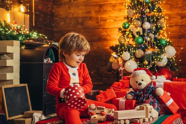 Il ragazzino felice sta giocando con le scatole regalo di natale sullo sfondo dell'albero di natale il bambino sta aspettando...