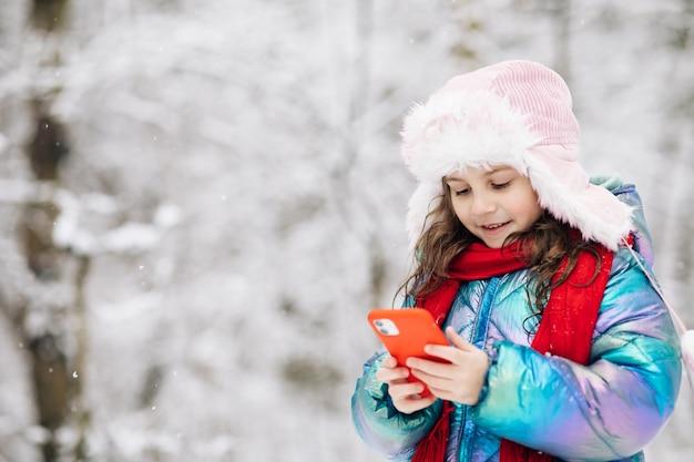 Il ragazzino felice usa l'app per la maschera facciale divertente per smartphone guarda lo schermo del cellulare sorride a qualcosa di divertente.