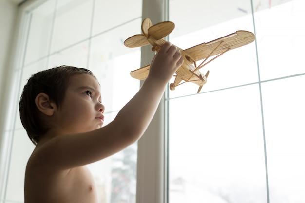 Felice ragazzino vuole volare con il suo aereo attraverso la finestra
