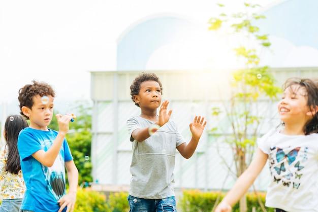 Bambini felici che soffiano le bolle di sapone nel parco di estate