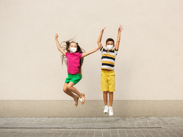 Bambini felici che indossano una maschera protettiva che saltano e corrono per le strade della città. sembra felice, allegro, sincero. copyspace. infanzia, concetto di pandemia. sanità, pandemia di coronavirus.