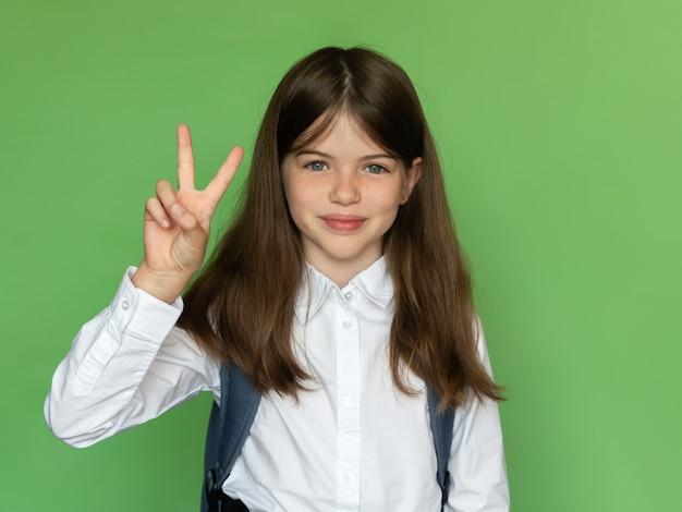 Piccola ragazza felice della scuola che mostra il segno v, torna al concetto di scuola