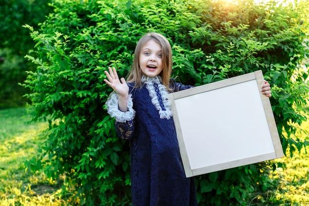 Felice piccola studentessa in possesso di un bordo bianco con spazio per il testo annuncio di scuola dell'inizio della formazione ritorno a scuola