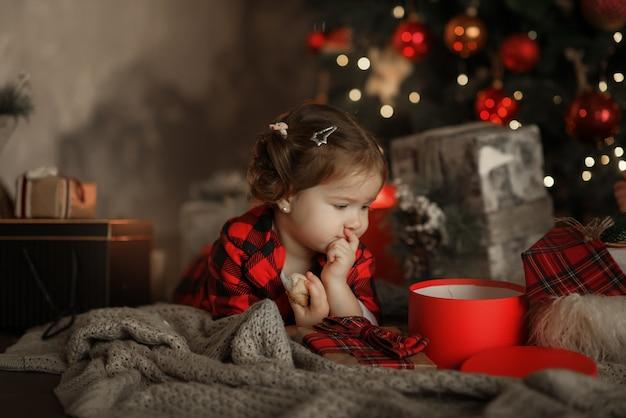 Bambina sorridente felice in pigiama rosso e cappello della santa con il contenitore di regalo di natale