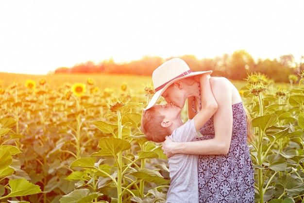 Piccolo figlio felice che bacia la madre incinta che sta sul campo soleggiato dei girasoli di fioritura. avvicinamento.