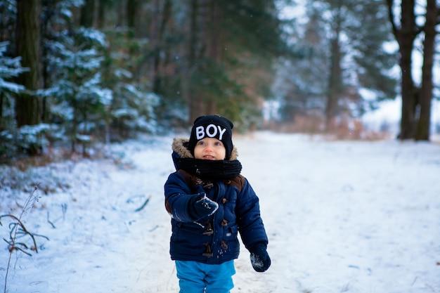 Piccolo ragazzo felice del bambino chiedendo i fiocchi di neve nella foresta di inverno