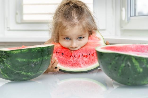Piccola ragazza felice del bambino che mangia anguria matura fresca per una sana colazione in una cucina familiare bianca e soleggiata.