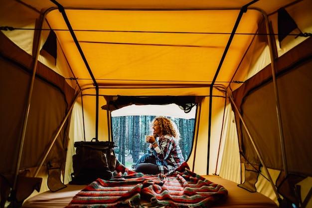 Felice e solitaria donna caucasica adulta si siede fuori da una tenda godendosi una tazza di tè