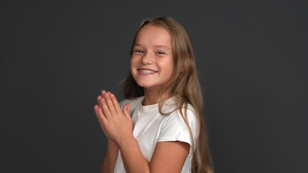 La ragazza teenager dai capelli lunghi felice sorride largamente che applaude le mani. bella studentessa caucasica con le parentesi graffe