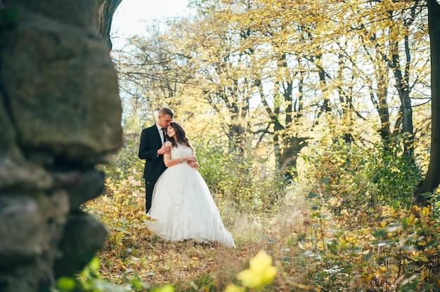 Lo sposo e la sposa felici e innamorati camminano nel parco in autunno il giorno delle nozze