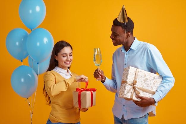 Coppia felice di amore in tappi che tengono bicchieri di bevande e scatole regalo, sfondo giallo. bella festa di famiglia, evento o festa di compleanno, decorazione di palloncini