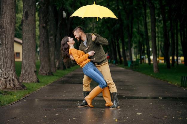 Coppie felici di amore che ballano nel parco in una giornata piovosa estiva. uomo e donna abbraccia sotto l'ombrello in caso di pioggia, appuntamento romantico sul percorso a piedi, tempo umido in vicolo