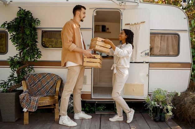 La coppia felice di amore tiene la disposizione vicino a camper, accampandosi in un rimorchio. l'uomo e la donna viaggiano in furgone, romantiche vacanze in camper, gli svaghi dei campeggiatori in camper