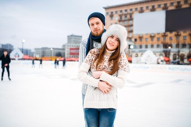 Abbracci felici delle coppie di amore sulla pista di pattinaggio