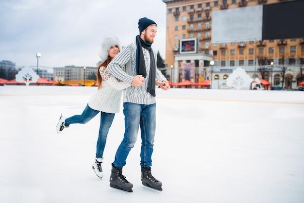 Le coppie felici di amore posa sulla pista di pattinaggio