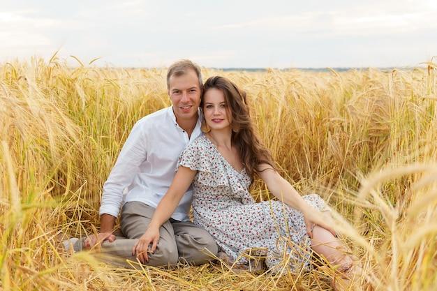 Coppia felice di amore che si siede nel grano sul campo. uomo e donna sul prato estivo