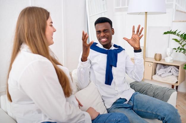 Felice coppia d'amore che parla sul divano di casa