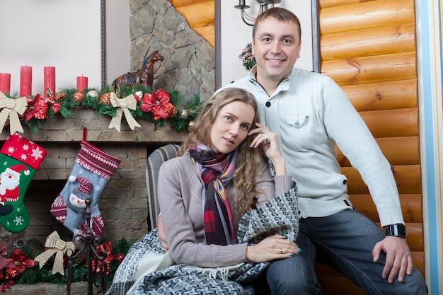 Felice coppia adorabile seduta sulla sedia vicino a un caminetto